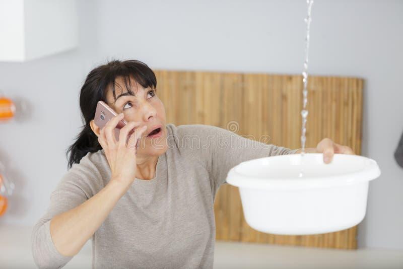 Kvinna som kallar och samlar vatten i hink fr?n tak arkivbilder