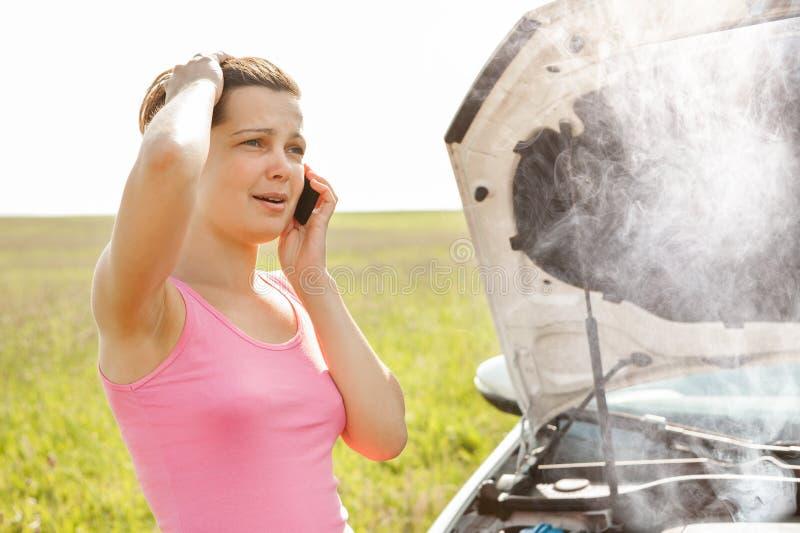 Kvinna som kallar p? mobiltelefonen n?ra avbrott ner bilen arkivfoton