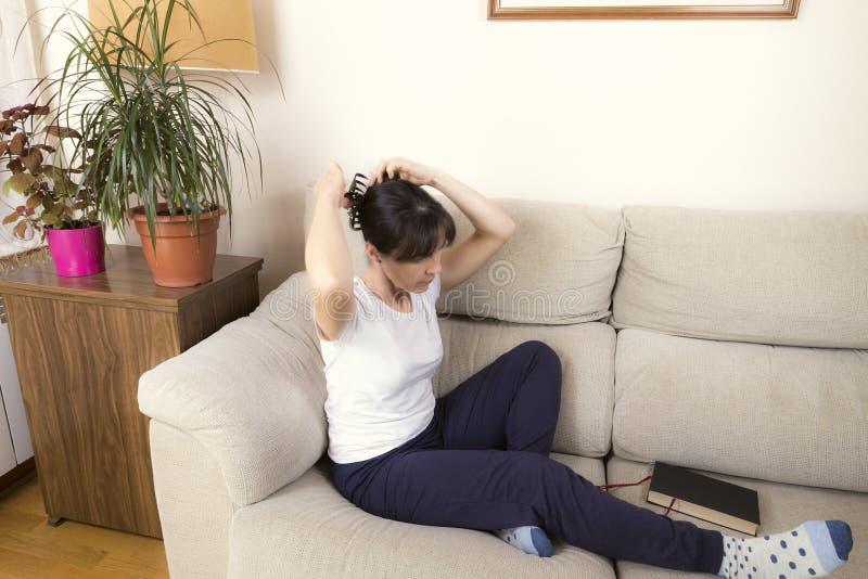 Kvinna som kammar bredvid en bok på en soffa arkivfoto