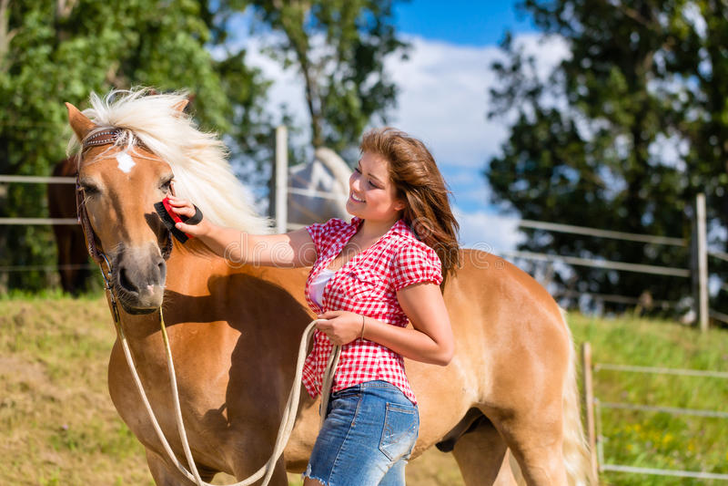 Kvinna som kammar ponnyn på häststall royaltyfri bild
