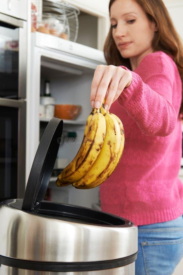 Kvinna som kastar bort omodern mat i kylskåp arkivbilder