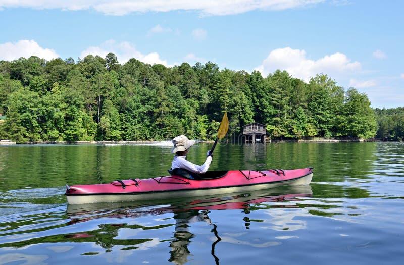 Kvinna som Kayaking på sjön arkivfoto