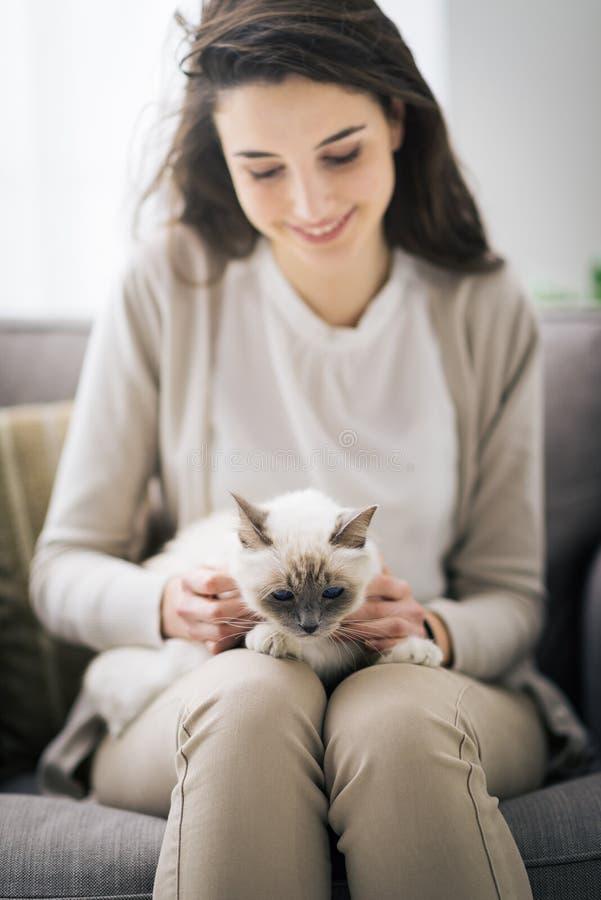 Kvinna som kelar hennes älskvärda katt royaltyfria foton