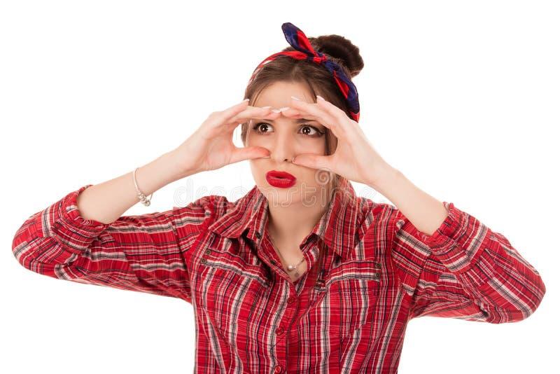 Kvinna som kikar att se till och med fingrar som kikare arkivbild
