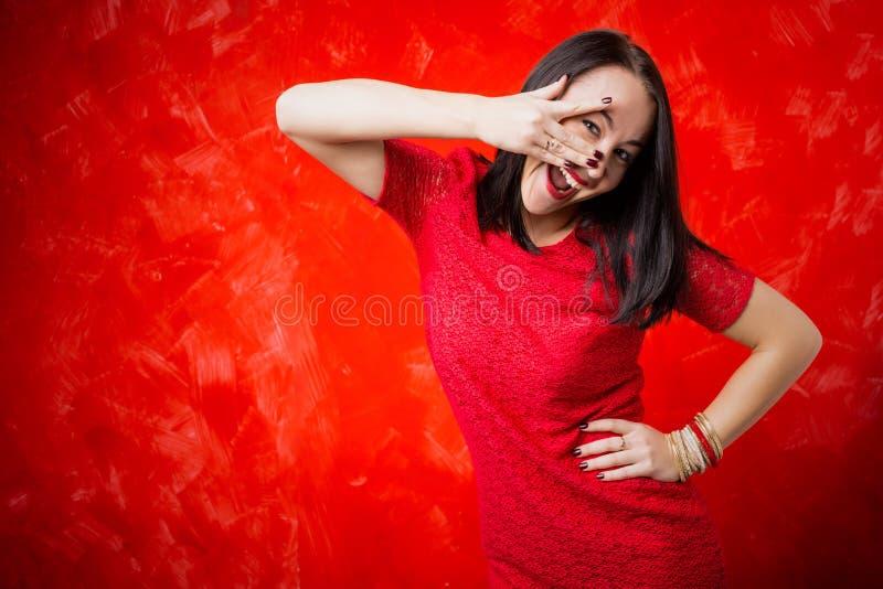 Kvinna som kikar till och med hennes fingrar arkivfoto