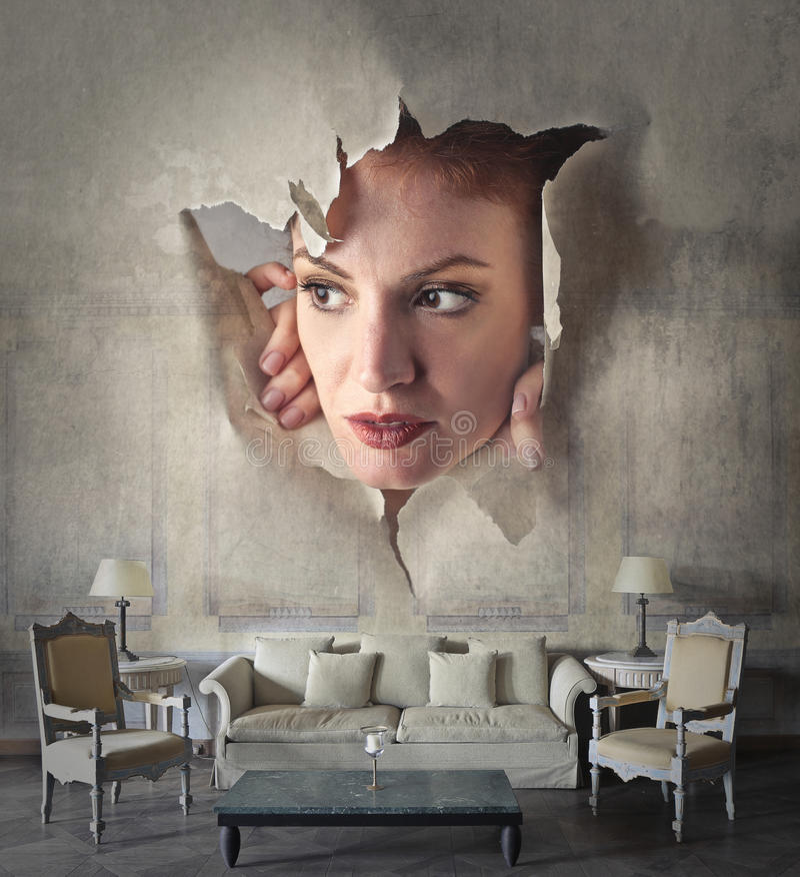Kvinna som kikar till och med väggen arkivfoto