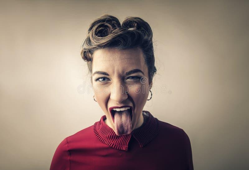 Kvinna som klibbar hennes tunga arkivfoto