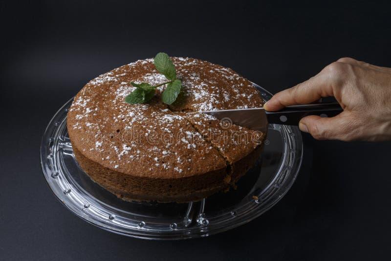 Kvinna som klipper en chokladkaka med sockergarnering med en kniv arkivbild