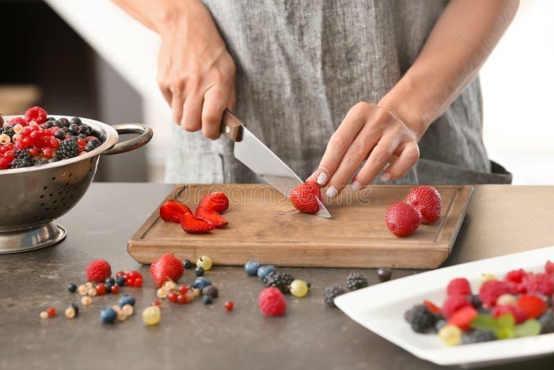 Kvinna som klipper nya mogna jordgubbar på tabellen arkivbild