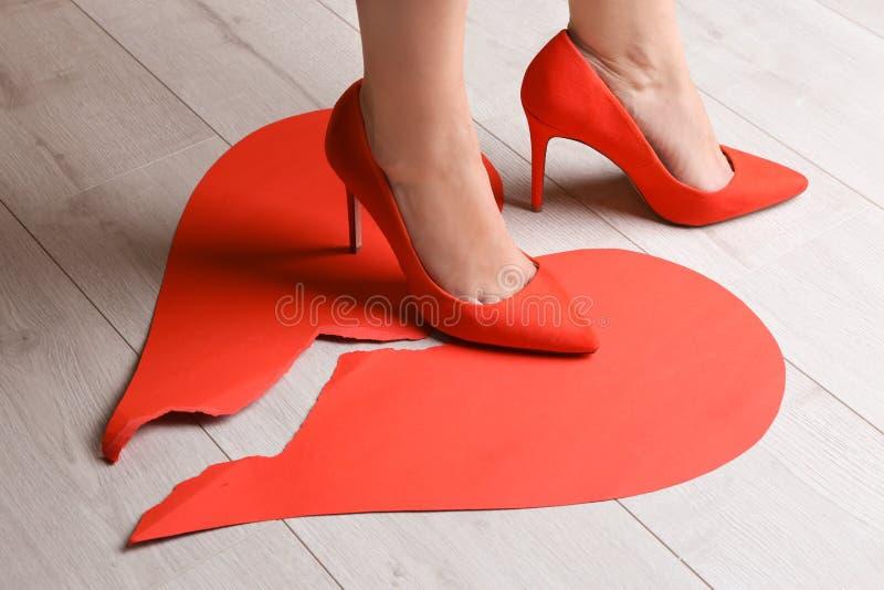 Kvinna som kliver på bruten pappers- hjärta på golv arkivfoto