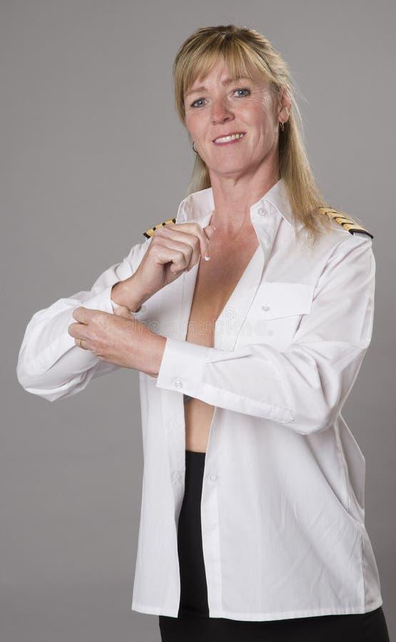 Kvinna som knäppas den vita skjortan arkivbilder