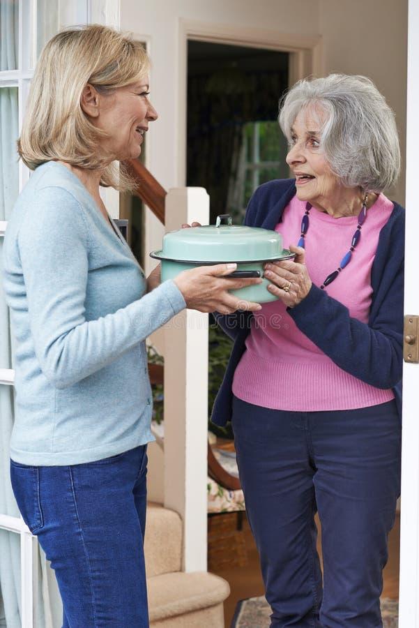 Kvinna som kommer med mål för äldre granne arkivfoto
