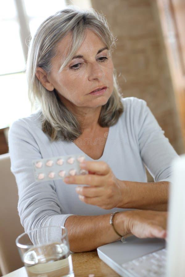 Kvinna som kontrollerar anvisningar på internet för medikament royaltyfri foto
