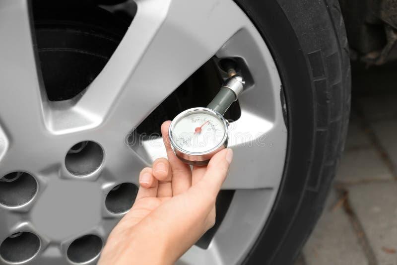 Kvinna som kontrollerar bilgummihjultryck med luftmåttet arkivfoton