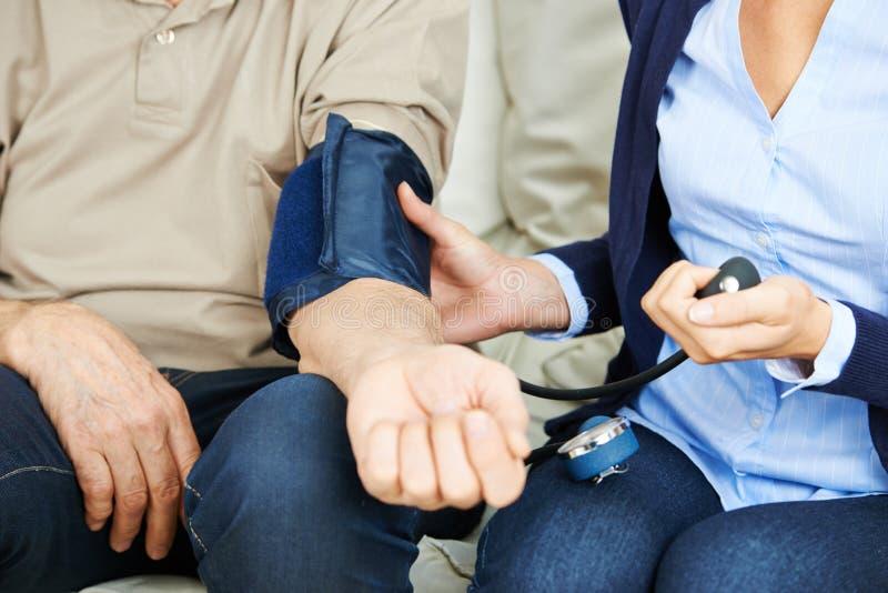 Kvinna som kontrollerar blodtryck av pensionären fotografering för bildbyråer