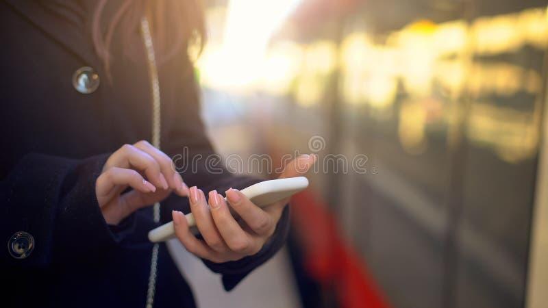 Kvinna som kontrollerar destinationspunkt på telefonen, genom att använda online-översikter för navigering royaltyfri fotografi