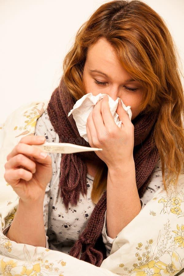 Kvinna som kontrollerar feaver med den digitala termometherflickan med influensa royaltyfri bild