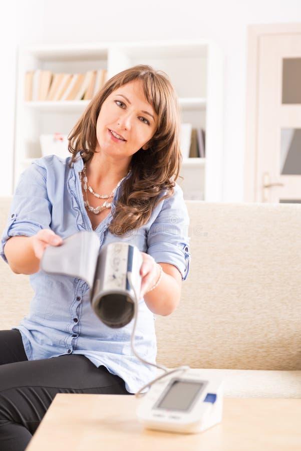 Kvinna som kontrollerar hennes blodtryck arkivbilder