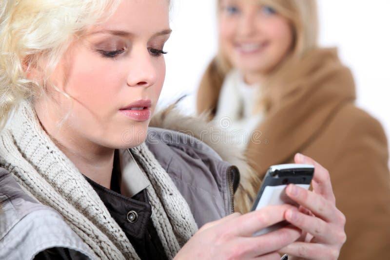 Kvinna som kontrollerar hennes mobiltelefon arkivfoton