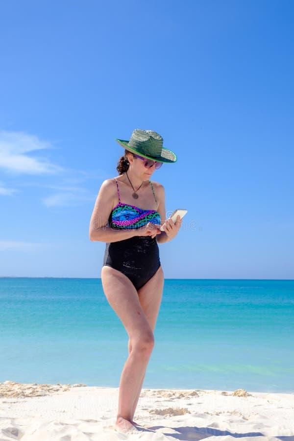 Kvinna som kontrollerar hennes mobiltelefon på stranden royaltyfria bilder