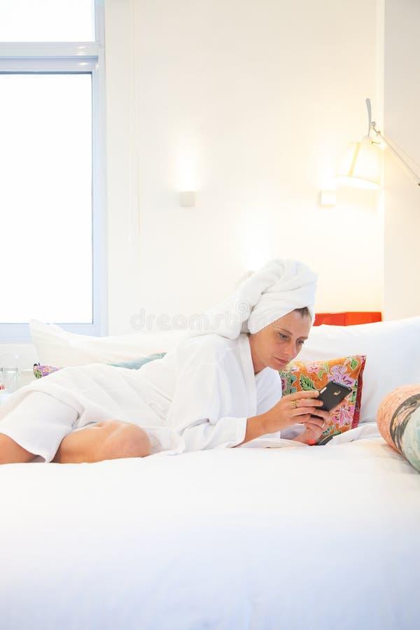kvinna som kontrollerar hennes telefon i sovrummet - socialt massmediaberoende arkivbild