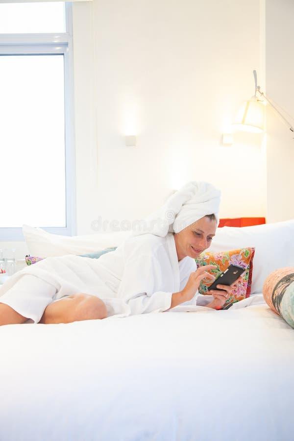 kvinna som kontrollerar hennes telefon i sovrummet - socialt massmediaberoende royaltyfria bilder