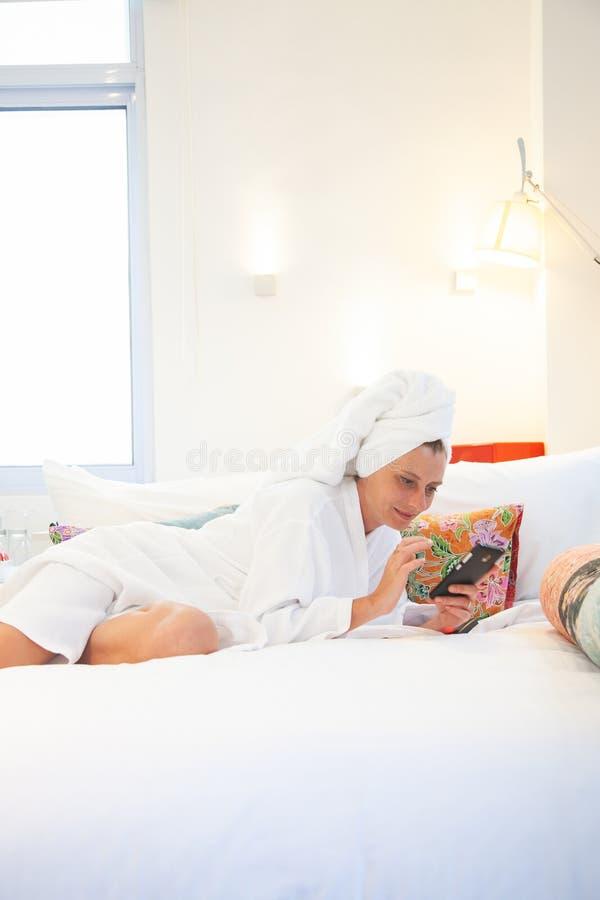 kvinna som kontrollerar hennes telefon i sovrummet - socialt massmediaberoende royaltyfria foton