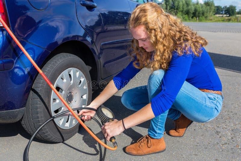 Kvinna som kontrollerar lufttryck av bilgummihjulet royaltyfria bilder