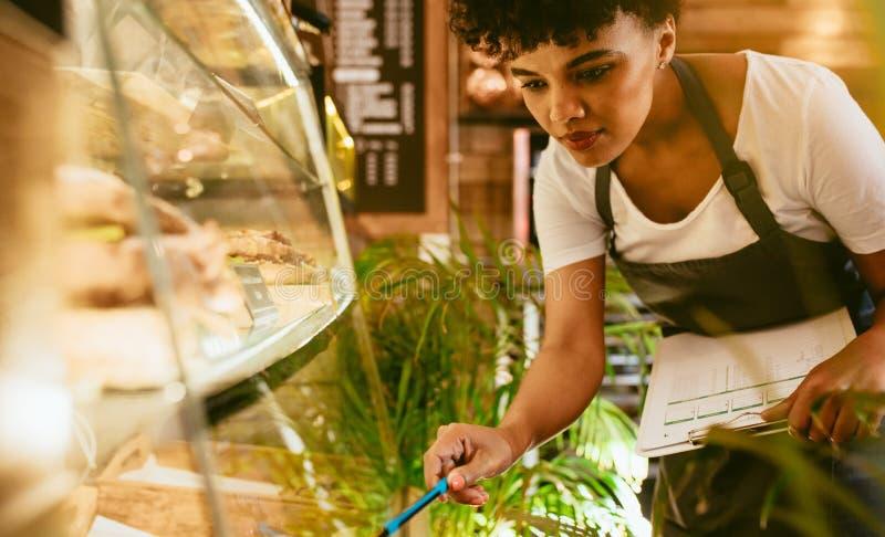 Kvinna som kontrollerar materielet i hennes kafé royaltyfria foton