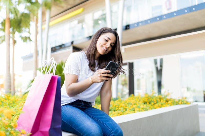 Kvinna som kontrollerar meddelanden på mobiltelefonen vid shoppingpåsar arkivfoto