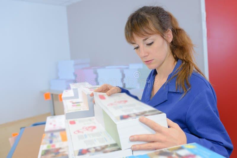 Kvinna som kontrollerar nya dokument på printinghuset arkivbild