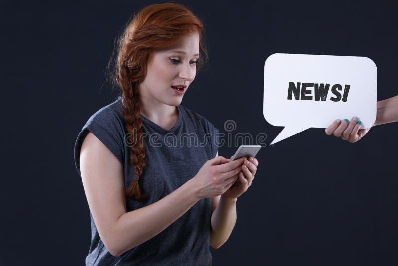 Kvinna som kontrollerar nyheterna royaltyfria foton