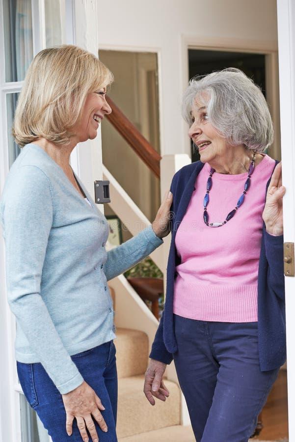 Kvinna som kontrollerar på äldre kvinnlig granne fotografering för bildbyråer
