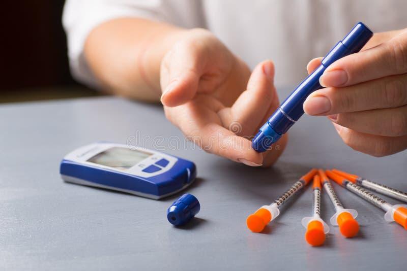 Kvinna som kontrollerar pennan för injektionsspruta för blodglukos den jämna användande med hem- glucometer royaltyfri foto
