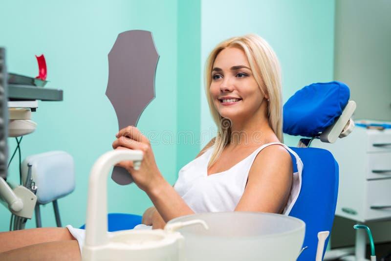 Kvinna som kontrollerar tänder i spegel Kvinnlig på tandläkarekontoret arkivfoto