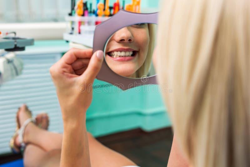 Kvinna som kontrollerar tänder i spegel Kvinnlig på tandläkarekontoret arkivbilder