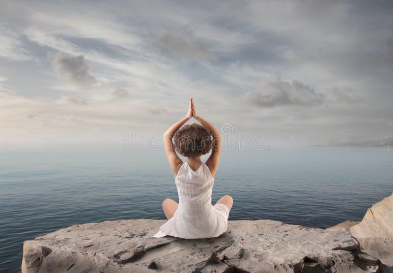 Kvinna som kopplar av göra yoga royaltyfria foton