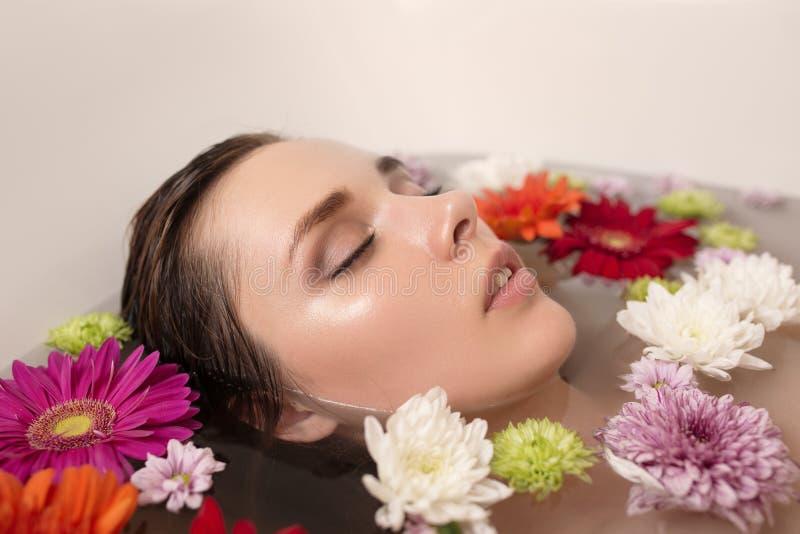 kvinna som kopplar av i bad med blommor royaltyfri bild
