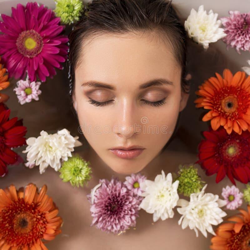 Kvinna som kopplar av i blommabad Spa royaltyfri bild