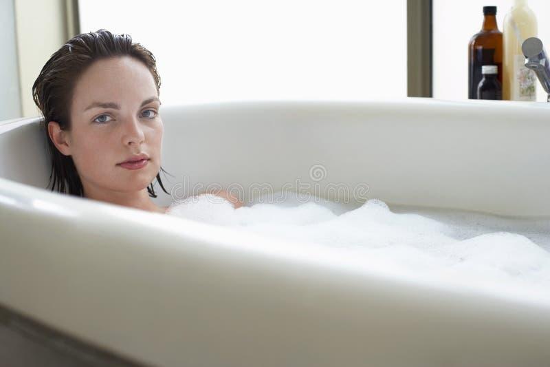 Kvinna som kopplar av i bubbelbad arkivbild