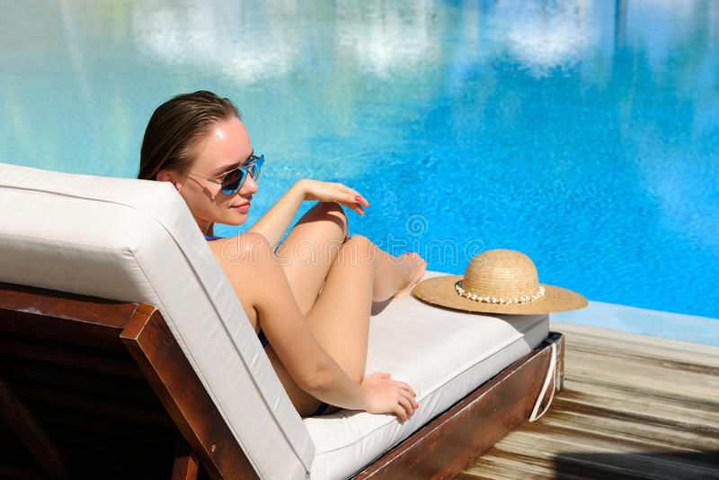 Kvinna som kopplar av på poolsiden arkivbild