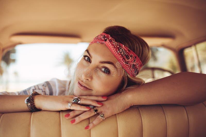 Kvinna som kopplar av i en gammal bil fotografering för bildbyråer