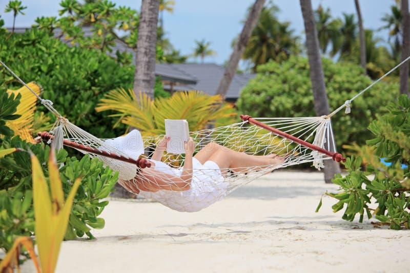 Kvinna som kopplar av i en hängmatta och en läsning en boka på en strand arkivfoton