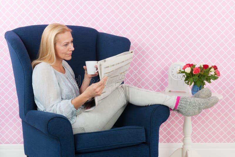Kvinna som kopplar av i läs- tidningar för stol arkivfoto