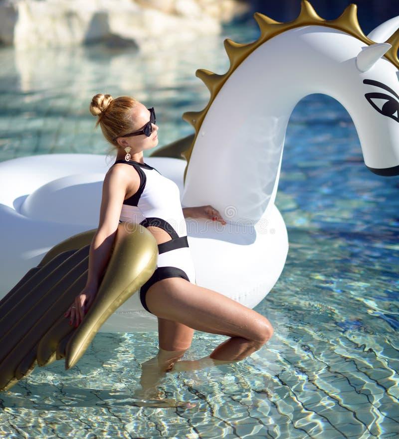 Kvinna som kopplar av i lyxigt simbassängsemesterorthotell med enorm bi arkivfoton