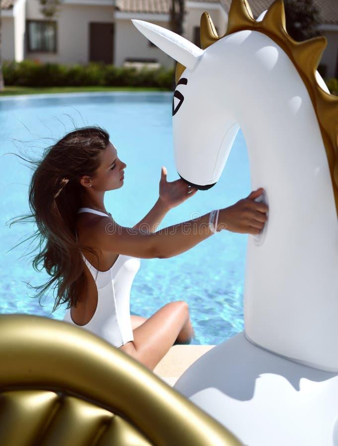 kvinna som kopplar av i lyxigt simbassängsemesterorthotell på den stora uppblåsbara enhörningen som svävar den pegasus flötet royaltyfri fotografi