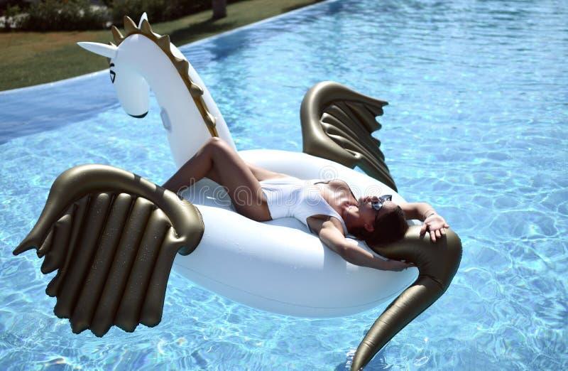 kvinna som kopplar av i lyxigt simbassängsemesterorthotell på den stora uppblåsbara enhörningen som svävar den pegasus flötet fotografering för bildbyråer