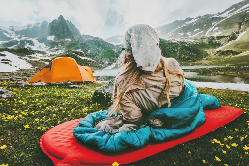 Kvinna som kopplar av i sovsäck på rött mattt campa royaltyfria bilder