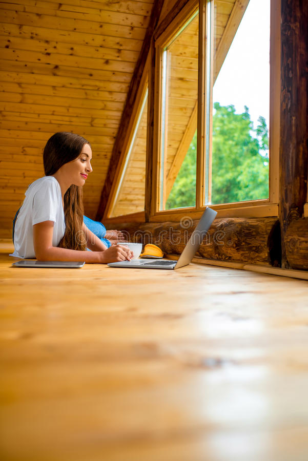 Kvinna som kopplar av i trähus arkivfoto