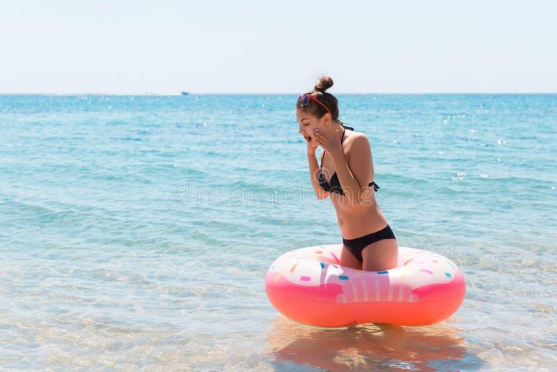 Kvinna som kopplar av med den uppbl?sbara cirkeln p? stranden chockad eller överraskningflicka i det kalla havet Sommarferier och royaltyfria bilder